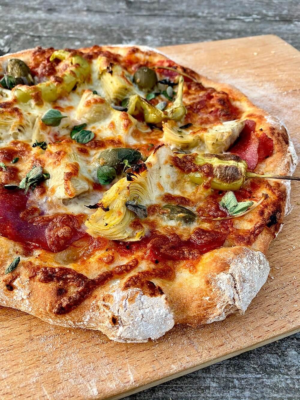 Meine persönliche Variante der Capricciosa ist die Pizza Rolfe mit San-Marzano-Tomaten, Salami, Artischocken, Apfelkapern, Peperoncini, gelbe Peperoni, Mozzarella und Oregano. Pizzateig selber machen.